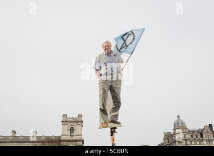 An image of veteran wildlife and environmental broadcaster Sir David Attenborough is held high in Parliament Square during the week-long protest by climate change activists with Extinction Rebellion's campaign to block road junctions and bridges around the capital, on 23rd April 2019, in London England. - Stock Photo