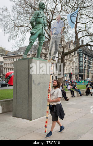 An image of veteran wildlife and environmental broadcaster Sir David Attenborough is held high in Parliament Square next to the statue of Field Marshal Jan Christiaan Smuts, the South African and British Commonwealth statesman, military leader and philosopher, during the week-long protest by climate change activists with Extinction Rebellion's campaign to block road junctions and bridges around the capital, on 23rd April 2019, in London England. - Stock Photo