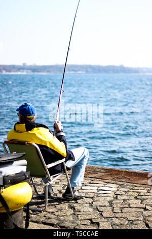 Fischersmann in schwarz-gelber Jacke sitzt an Kieler Förde mit Angel und fängt Fische - Stock Photo
