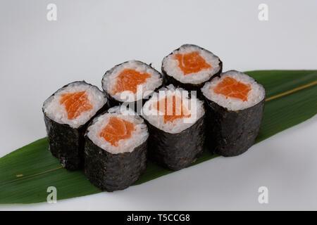 Sake maki Japanese sushi rolls with salmon on banana leaf on white background - Stock Photo