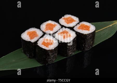 Sake maki Japanese sushi rolls with salmon on banana leaf on black background - Stock Photo