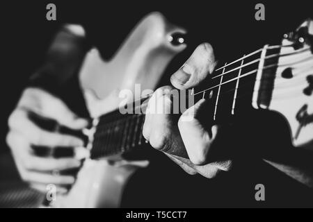 Man playing electric guitar close up. Black and white. Practicing guitar and playing solo - Stock Photo
