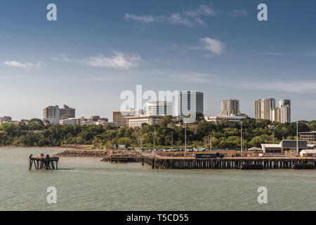 Darwin Australia - February 22, 2019: South side downtown skyline seen from harbour waters. Dock up front. Blue sky and greenish water. - Stock Photo