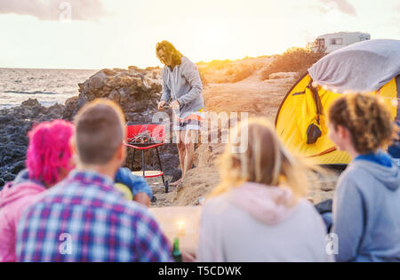 Group of happy friends camping with tent on the beach and preparing a barbecue dinner - Young people having fun making bbq and drinking beer - Stock Photo