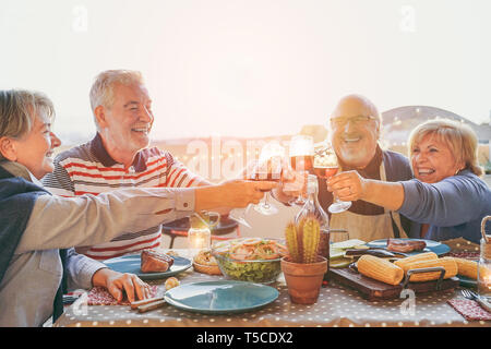 Happy senior friends having fun cheering with red wine at barbecue in terrace  outdoor - Mature people making dinner toasting glasses - Stock Photo