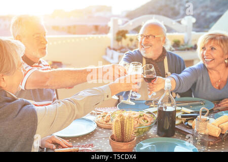 Happy senior friends having fun cheering with red wine at barbecue in terrace outdoor - Older people making  dinner toasting glasses - Stock Photo