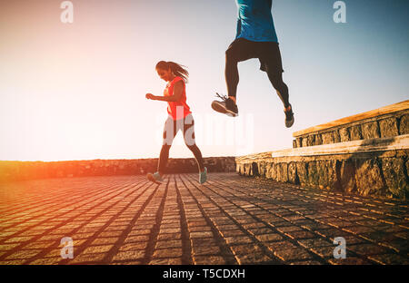 Health fit young couple running together during a magnificent sunset - Athletic friends doing sport outdoor - Stock Photo