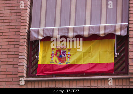 Spanish flag hanging from a balcony in a Spanish state city to indicate Spanish national patriotic fervor - Stock Photo
