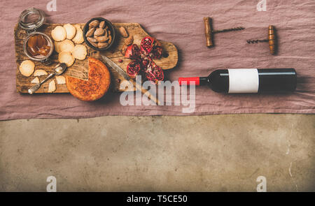 Wine bottle, vintage corkscrews and appetizers on board, copy space - Stock Photo