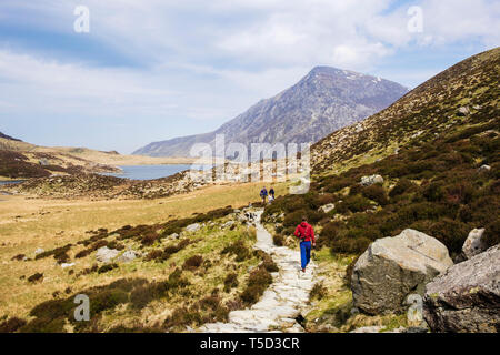 People walking on the path around Llyn Idwal lake in in Cwm Idwal valley in Snowdonia National Park. Ogwen, Conwy, Wales, UK, Britain - Stock Photo