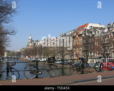 A typical Dutch scene with a row of bicycles parked against the railings on a bridge over a canal in the centre of Amsterdam - Stock Photo