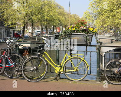 A bicycle with a yellow frame stands out amongst the others parked against the railings on a canal bridge in Amsterdam; April 2019 - Stock Photo