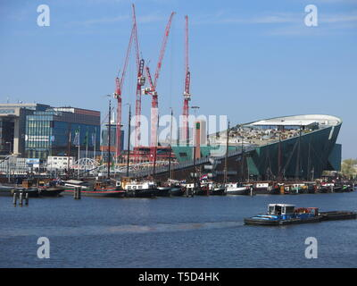 View from across the harbour of the impressive giant green hull of the boat-shaped building for NEMO Science & Technology museum in Amsterdam - Stock Photo
