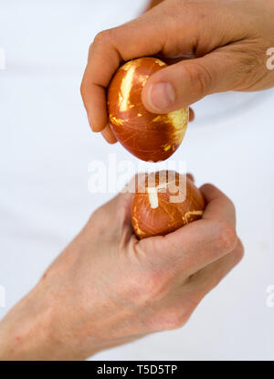 male and female hand tapping naturally colored eggs during Easter over a white background - Stock Photo