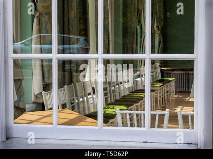 A view through a window  into the assembly rooms in Royal Lemington Spa showing empty chairs with an atmosphere of sadness - Stock Photo
