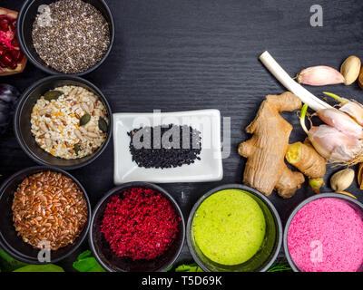 Vegan health food selection with mixed seeds, flax, sesame, sunflower and pumpkin seeds, chia, black cumin, strawberry, raspberry powders, ginger, gar - Stock Photo