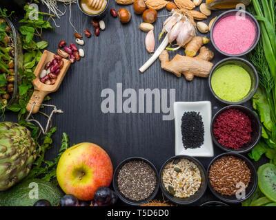 Balanced diet food raw seeds, beans, superfoods, vegetables, microgreens on dark wooden table top view. Vegetarian or diet food - Stock Photo