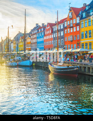 Nyhavn view with boats by embankment at sunset, people walking and sitting in restaurants, Copenhagen, Denmark