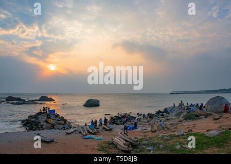 Horizontal view of people enjoying the sunset in Kanyakumari, India. - Stock Photo
