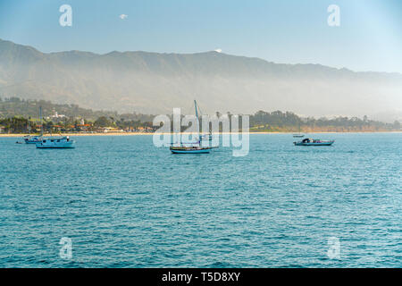 Foggy Morning in Santa Barbara. Quiet Pacific Ocean, Boats, Sand Beach, and Mountains on a Horizon - Stock Photo