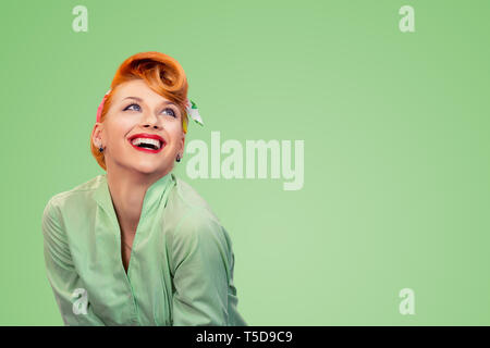 Closeup red head young excited woman pretty pinup girl green button shirt smiling laughing looking up isolated on yellow background retro vintage 50's