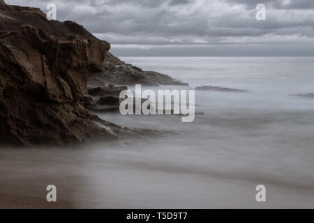 Pacific shoreline with silky smooth water rolling in and out with the surf. Sunset long exposure with silky smooth water at the beach. - Stock Photo