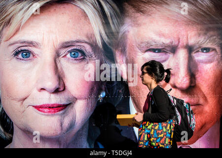 People walks past two portraits of the presidential candidates, pasted on a CNN Airstream trailer outside the debate area. The Democrate and Republican nominees for US President, Hillary Rodham Clinton and Donald John Trump, met on Sep. 26th for the first head to head Presidential Debate at the Hofstra University in Long Island. - Stock Photo