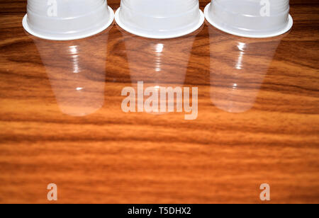 empty three plastic cups standing on wooden table with reflection - Stock Photo