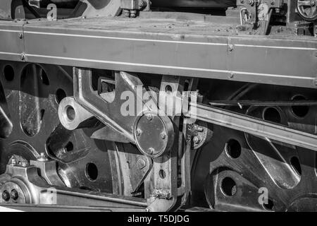 Black and white, close-up photograph of british, vintage steam locomotive wheels. Side view of steam train driving wheels with connecting coupling rod. - Stock Photo