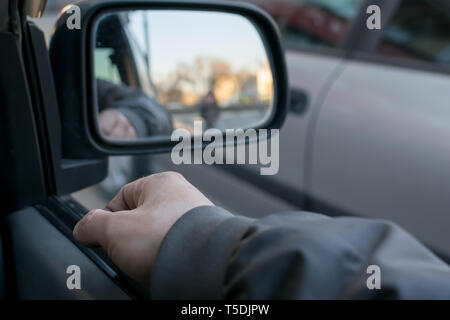 a man's hand on the car door on the background of a female silhouette in the mirror of the rear view mirror - Stock Photo