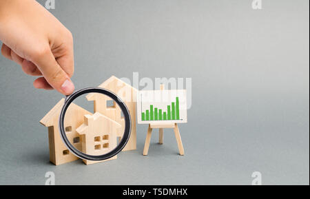 Magnifying glass is looking at the Wooden houses with a stand of graphics and information. Growing demand for housing. growth of city and its populati - Stock Photo