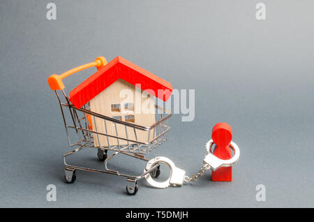 A person is handcuffed to a house on a supermarket cart. The concept of a large debt on a loan or mortgage. Financial dependence, unavailable housing  - Stock Photo