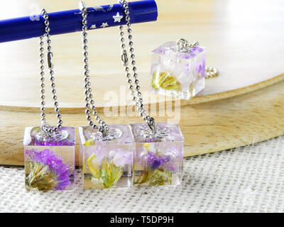 Dried flower in crystal clear resin pendant necklace, pendant with a real flowers. - Stock Photo