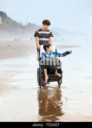 Young man pushing disabled twelve year old brother in wheelchair on a misty foggy beach by the ocean - Stock Photo
