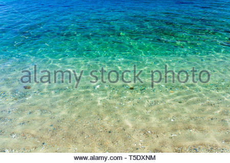 Cristal clear pristine turquoise and blue tropical water with white sand, cobbles and shells in Aninuan beach in Puerto Galera, Philippines - Stock Photo