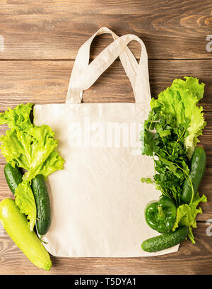 Fresh green vegetables zucchini cucumber greens in eco bag made of natural cotton wooden background. Healthy food - Stock Photo