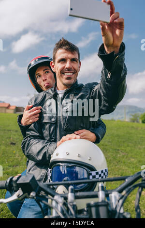 Young couple taking a selfie on the motorcycle outdoors - Stock Photo