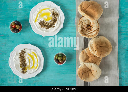 labneh labaneh)middle eastern soft goat's milk cheese with olive oil, za'atar, lemon,pita bread ,served at traditional concept over rustic wooden tabl - Stock Photo