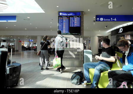 Passengers travellers awaiting flight looking at electronic departures display & sitting in Bristol airport with bags to go on holiday in Europe 2019 - Stock Photo