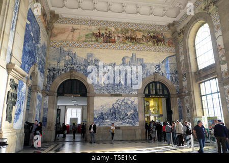 Passengers queue beneath azulejos blue tiles on walls to buy train tickets inside Sao Bento Railway Station in Porto Portugal Europe   KATHY DEWITT - Stock Photo
