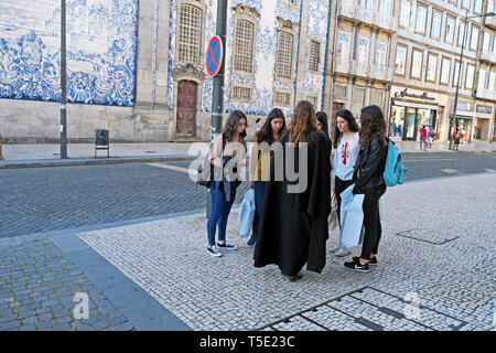 University female student in black cloak talking to friends in street Igreja do Carmo near Praça de Carlos Alberto Porto Portugal Europe KATHY DEWITT - Stock Photo