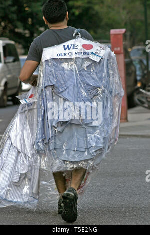 Man on the street carrying his shirts picked-up from a dry cleaner - Stock Photo