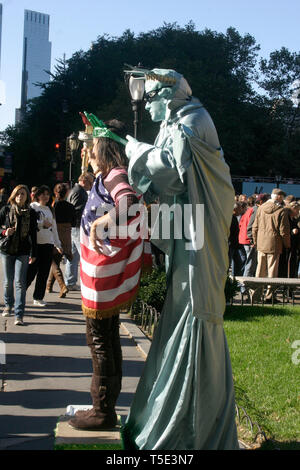 People taking pictures with person dressed as the Statue of Liberty in New York City, USA - Stock Photo