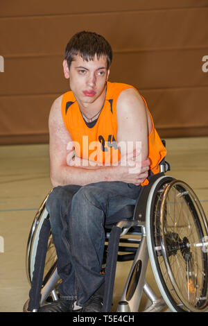 Handicapped boy with sports shirt sitting in a sports wheelchair - Stock Photo