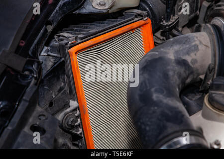 Close-up on a dirty air filter for an engine with an orange frame installed in the engine compartment of a premium car during vehicle maintenance in a - Stock Photo