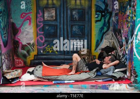 Homeless man oblivious to the street art in Hosier Lane, Melbourne - Stock Photo