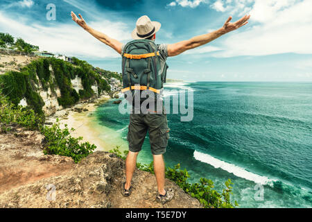 Man Traveler on mountain summit enjoying aerial view hands raised over clouds Travel Lifestyle success concept adventure active vacations outdoor - Stock Photo