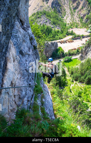 Female climber hanging from a via ferrata cable on 'Astragalus' route, a popular tourist attraction in Bicaz Gorge (Cheile Bicazului), Neamt county, R - Stock Photo