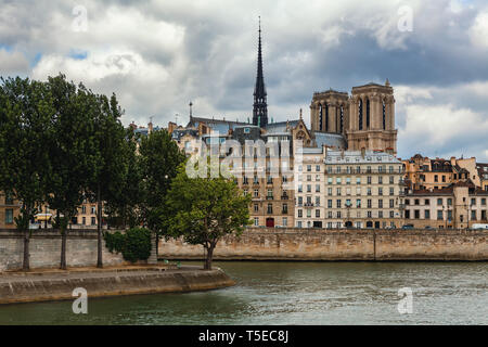 View of Seine river and spire of famous Notre-Dame de Paris cathedral among typical parisian buildings under cloudy sky. Stock Photo