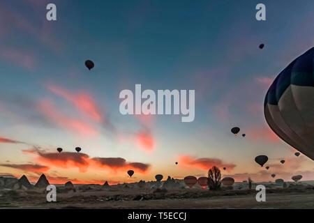 Sunrise at Cappadocia with many hot air balloons flying - Stock Photo